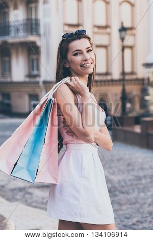 Beautiful shopaholic. Beautiful young woman carrying shopping bags and looking over shoulder with smile while standing outdoors