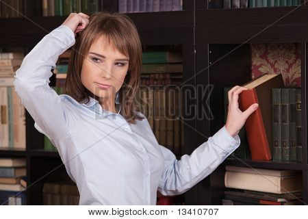 Young Woman With Book In Library.