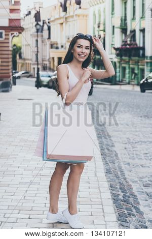 That was a great day shopping. Full length of beautiful young woman carrying shopping bags and looking away while standing outdoors