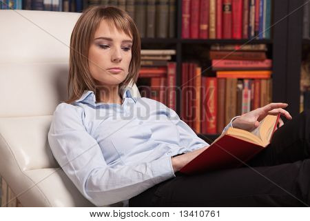 Clever Young Woman Reads Book At Home.