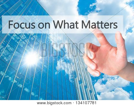 Focus On What Matters - Hand Pressing A Button On Blurred Background Concept On Visual Screen.