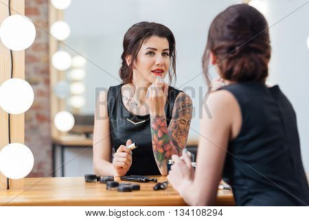 Beautiful tattooed young woman applying red lipstick in dressing room