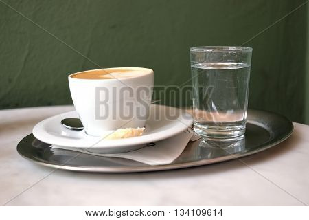 A cup of cappuccino coffee and a glass of mineral water on the table