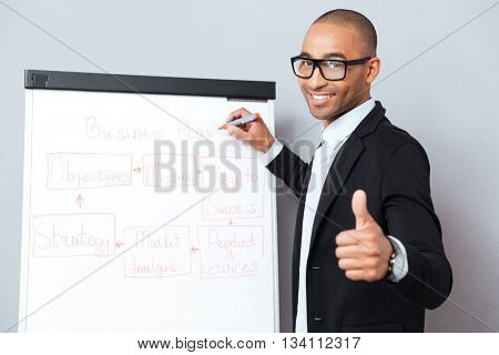 Happy african young man in glasses writing on flipchart and showing thumbs up