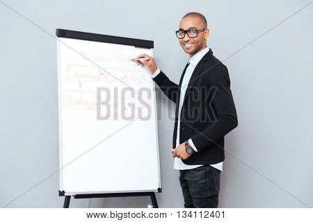 Smiling african young man in glasses writing business plan on flipchart