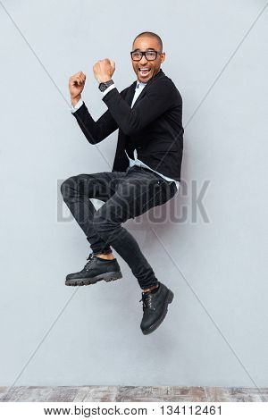 Happy excited african american young man jumping and celebrating success