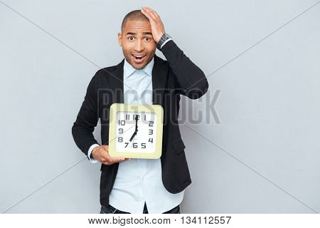 Amazed worried african american young man standing and holding clock