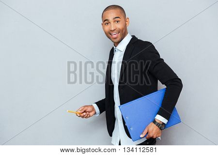 Happy young businessman walking holding blue folder and pencil
