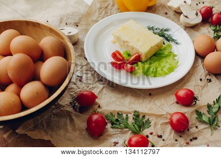 Omelet with ham on parchment background. Vegetable composition.