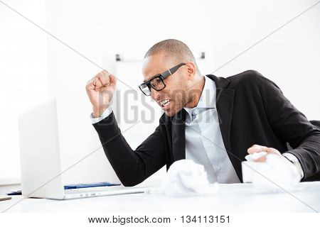 Angry nervous businessman working at office desk overloaded with paperwork