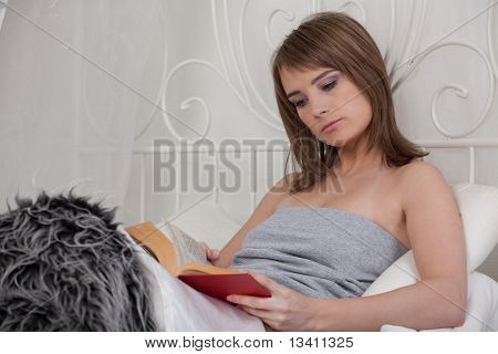 Young Woman Reads Book In Bedroom.