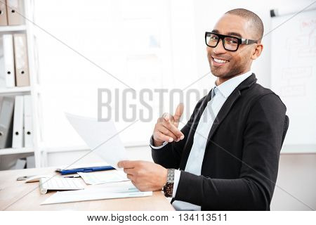 Handsome young businessman pointing finger at camera and holding papers in office