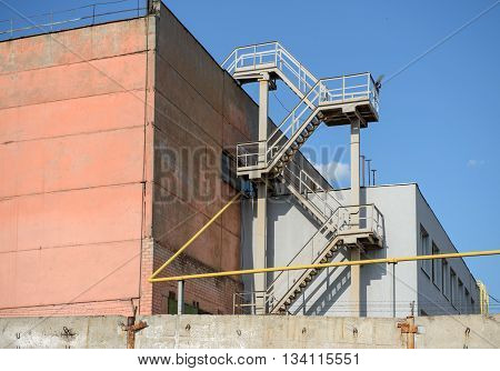 Outdoor corner of old industrial building with metal fire escape in the corner and yellow pipeline are in sunlight.