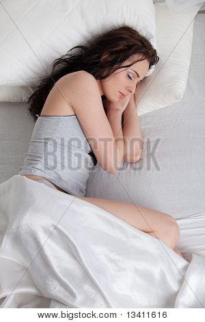 Junge Frau schläft im Bett zu Hause.