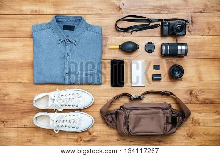 Travel concept shirt, camera, mobilephone, bag, mp3, boots on the desk