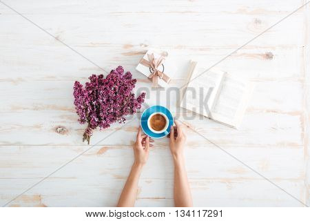 Hands of young woman drinking coffee and reading book on wooden table with flowers and present box