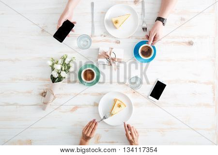 Hands of young couple eating cakes and using blank screen smartphones on wooden table with cups of coffee, present box and flowers