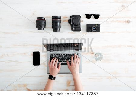Hands of young man using laptop on wooden table with blank screen mobile phone, glass of water, sunglasses, lenses and photo camera