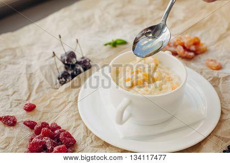 Millet porridge with pumpkin and oil spoon. Parchment background