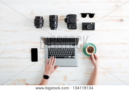 Hands of young man using laptop and drinking coffee on wooden table with blank screen mobile phone, sunglasses, lenses and photo camera