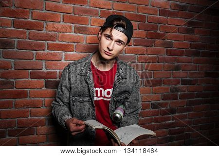Graffiti man in cap holding sketchbook isolated over red brick wall
