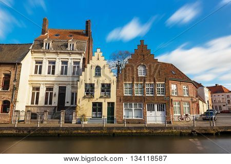 Bruges (Brugge), Belgium - February of 2016: Old belgian street with traditional varicolored houses and water canal