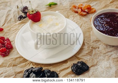 Rice porrige with strawberry on parchment background.