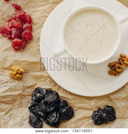 Oat meal with walnuts and berries. Parchment background. Flat Lay