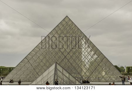 PARIS, FRANCE - MAY 18, 2016: Tourists around the pyramids at the famous Louvre Museum. Tourism in Paris has not suffered as a result of the terrorist attacks of 2015.
