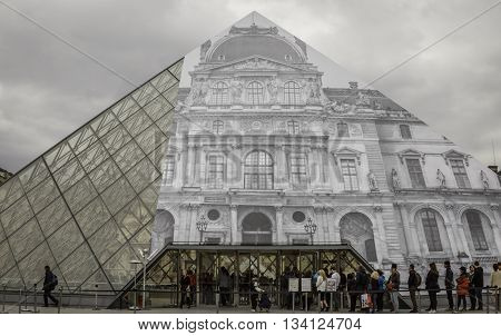 paris, france - may 18, 2016: tourists in a queue at the louvre pyramid to purchase tickets to the louvre museum. tourism in paris has not suffered as a result of the 2015 terrorist attacks.