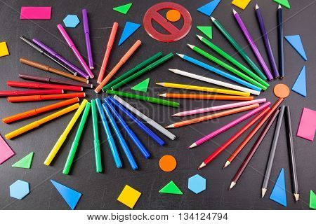 A lot of colorful felt-tip pens and colorful pencils in circles and geometric figures on the black school chalkboard as background concept