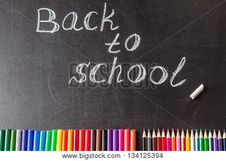 Back to school background with colorful felt tip pens pencils and the title