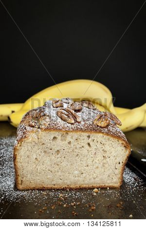 Banana bread with pecans.  Fresh-baked, over dark background.