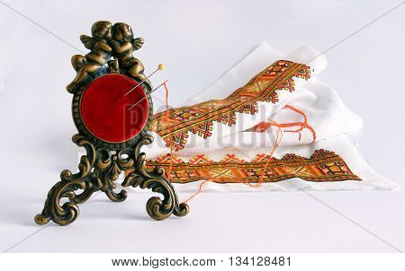 An antique red pincushion in a bronze frame with angels against the background of embroidery