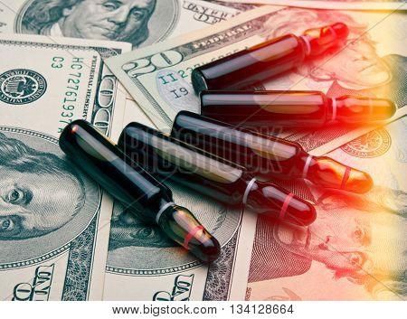 vials with a medical drug on a background of dollar bills