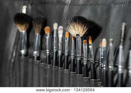 Makeup brushes of different sizes and shapes in row, professional fashion cosmetic tools in compact case of black leather, selective focus