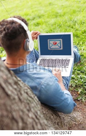 Cheerful young man is using a laptop in park. He is sitting and leaning back on tree. The student is listening to music from headphones with enjoyment