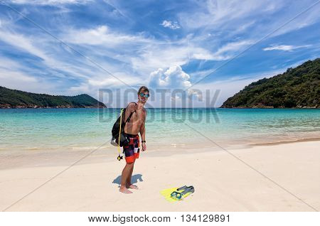 Male scuba diver shows the thumbs up sign on a tropical beach