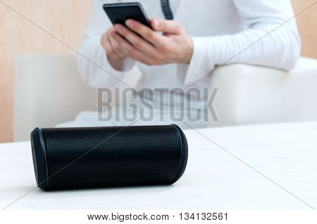 Man is using his smartphone application to connect with wireless speaker.