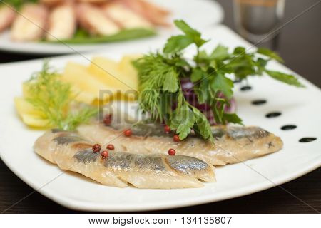Fillet herring with vegetables on the white