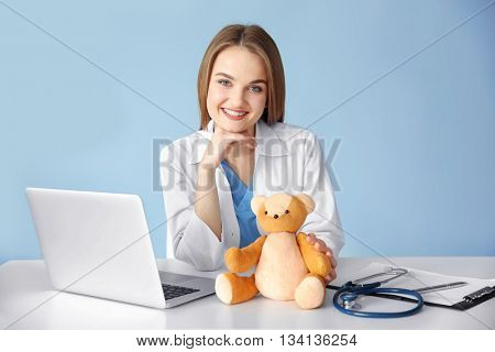 Young beautiful female doctor at the table on wall background