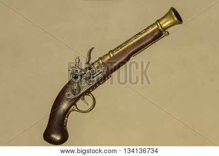 Vintage gun souvenir Brown with bronze on a beige background