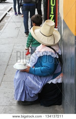 Cajamarca Peru - June 11 2016: Andean woman in traditional dress sells cheese on the street in Cajamarca Peru on June 11 2016