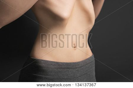 Belly of young woman with anorexia on dark background