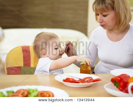 mother feeding a baby at home