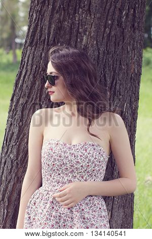 girl with red lips in the sundress and in the black glasses looks aside on the tree background