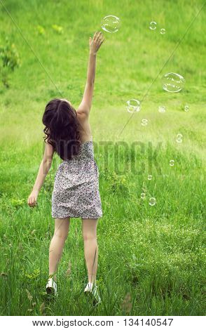 the girl in a light sundress reaches out for soap bubbles on a green grass background