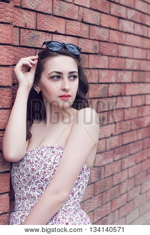 girl with red lips in the sundress looks aside on the brick wall background