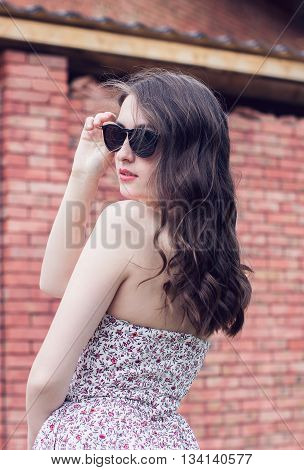 girl with red lips in the black glasses and in the sundress turns around on the brick wall background