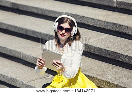 Student girl or young woman listen music from tablet pc outdoors. Girl with earphones wears sunglasses sit at downstairs. Music leisure. Having fun, relax outdoors. Girl with device, internet music